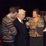 <p>Leonardo Poli e il genero Marco, ricevono da Maria Grazia Vacchina il premio alla memoria di Cecilia Poli</p>